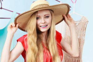 blond teenager on vacation wearing a sun hat and smiling with her braces
