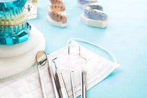 Dental models of teeth, dental tools, and braces on a dental model